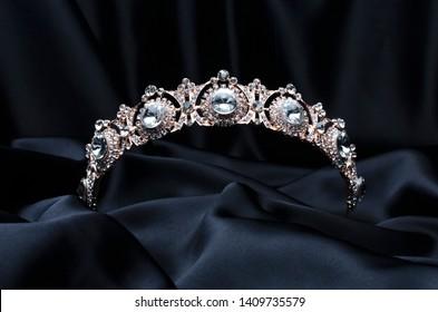 golden tiara with diamonds on a black silk