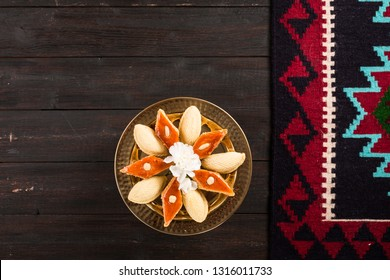 Golden tray with shekerbura and pakhlava for Novruz, Azerbaijan traditional pastry for spring equinox and Persian Nowruz, Navruz new year celebration on dark brown wooden background with rug carpet