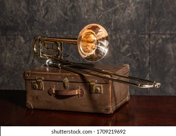 Golden trombone musical instrument lies on an old suitcase