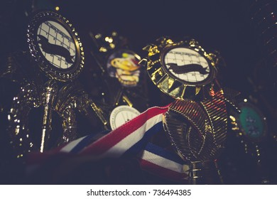 Golden trophies and medal ribbon close up background