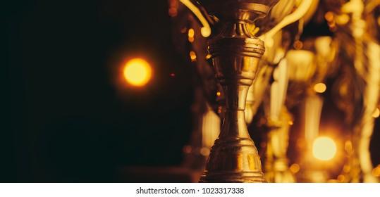 Golden trophies on dark background.