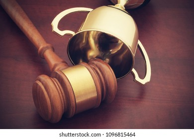 Golden trophy cup and gavel on wooden background, court of arbitration for sport concept