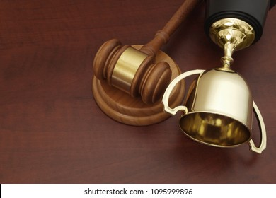 Golden trophy cup and judge gavel on wooden background with copyspace
