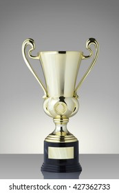 Golden trophy cup on gray background