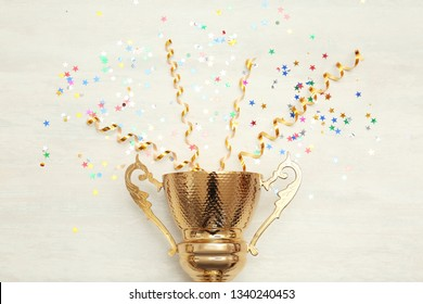 Golden trophy cup and streamers on wooden background, top view