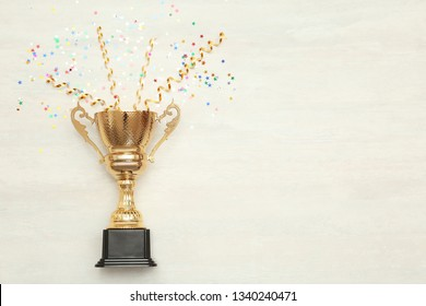 Golden trophy cup and streamers on wooden background, top view with space for text