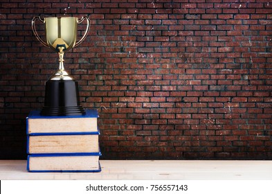 Golden Trophy on stack of books over brick background