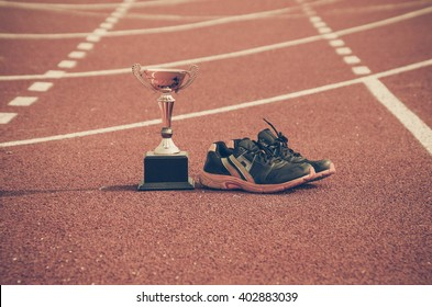 A golden trophy and running shoes on running race lane