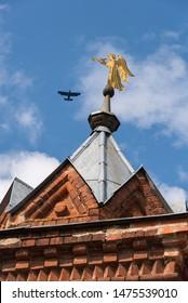 Golden trumpet angel on brick wall tower,  Chernigovsky skete of the Holy Trinity Sergius Lavra  in Sergiev Posad, Russia