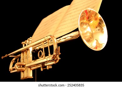 Golden trumpet on black background with sheet music as seen from the front and low.
