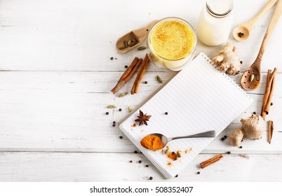 Golden turmeric latte in a glass, spices and recipe book over white wooden background with copy space