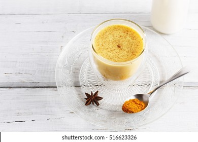 Golden turmeric  latte over white wooden table with copyspace