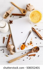 Golden turmeric latte, spices and recipe book over white wooden background. Top view