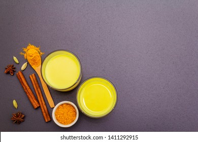 Golden turmeric milk. Cinnamon, cardamon, anise spices. Trendy healthy drink concept. In glass on stone background, top view, copy space
