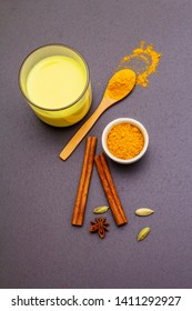 Golden turmeric milk. Cinnamon, cardamon, anise spices. Trendy healthy drink concept. In glass on stone background