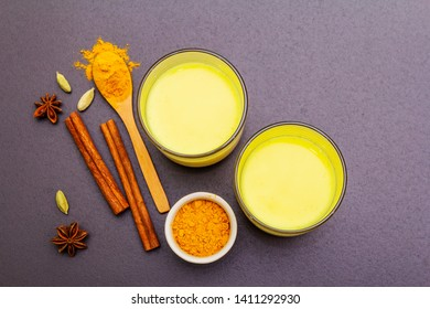 Golden turmeric milk. Cinnamon, cardamon, anise spices. Trendy healthy drink concept. In glass on stone background, top view