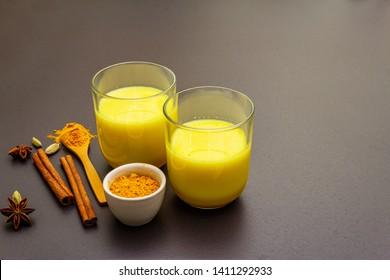 Golden turmeric milk. Cinnamon, cardamon, anise spices. Trendy healthy drink concept. In glass on stone background, copy space
