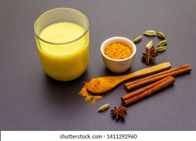 Golden turmeric milk. Cinnamon, cardamon, anise spices. Trendy healthy drink concept. In glass on stone background, close up