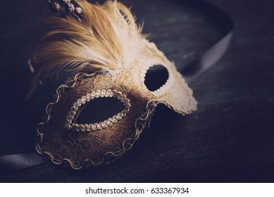 Golden venetian ball mask over dark background with copyspace. Masquerade party or holiday event celebration concept.