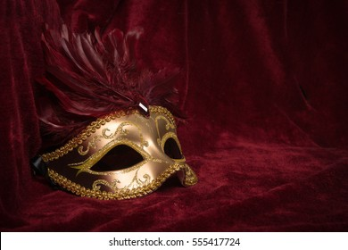 Golden venetian carnival mask with red feathers seen from the side on a draped red velvet theater curtain
