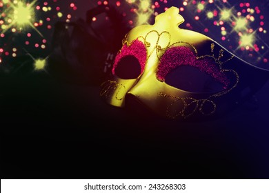 Golden venetian mask over black background.
