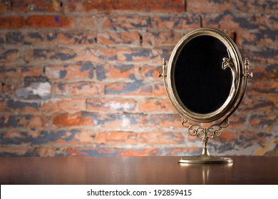 Golden vintage mirror on wood table