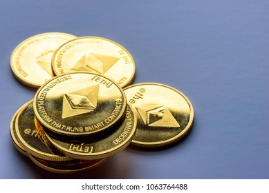 Golden virtual money Ethereum crypto currency coins stacked on a dark background