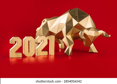 Golden volumetric paper bull papercraft and numbers 2021 on a red background, symbol of the year
