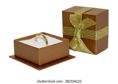 Golden wedding ring in open gift box, box cover with ribbon and bow, isolated on white background