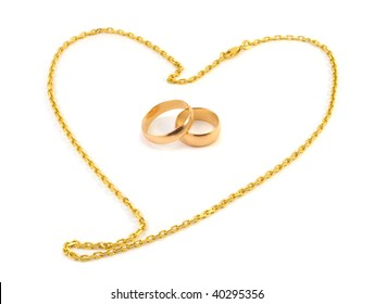 Golden wedding rings with a chain composed of a heart on a white background