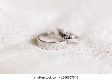 Golden wedding rings with diamond on white lace background. Wedding details. Traditional accessory, symbol of love and marriage.