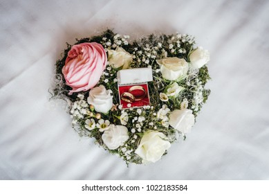Golden wedding rings in a floral bouquet with white and pink roses