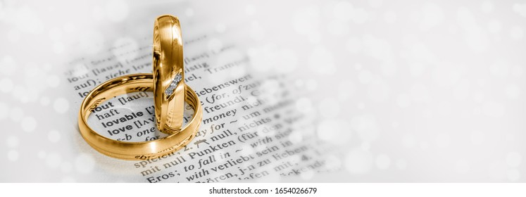 "Golden wedding rings frame the word ""love"" in a lexicon, white bokeh in the banner background"