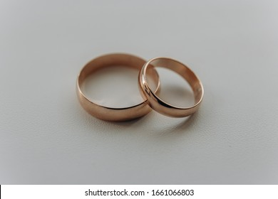 golden wedding rings lie on a white background