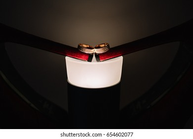 Golden Wedding Rings Lie On The Lamp And Heels Of Red Shoes