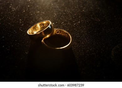 Golden wedding rings with newlyweds names inside lie on black cover