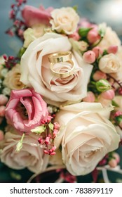 Golden wedding rings on a bridal bouquet with pink roses