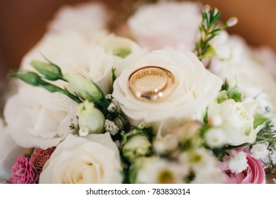 golden wedding rings on a bridals bouquet