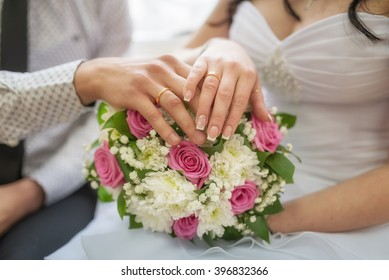 Golden wedding rings on bride and groom fingers with flowers