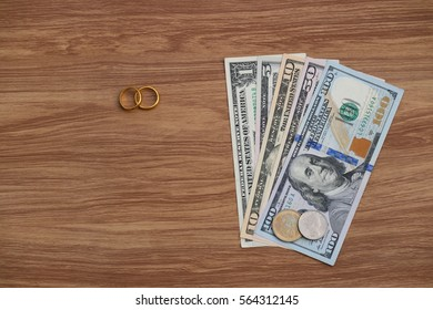 Golden wedding rings on Dollar banknotes cash background. Marriage of convenience, love and finance concept