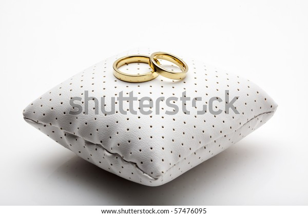 golden wedding rings on small white leather cushion