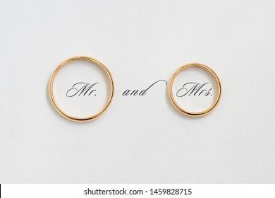 Golden wedding rings on white paper.