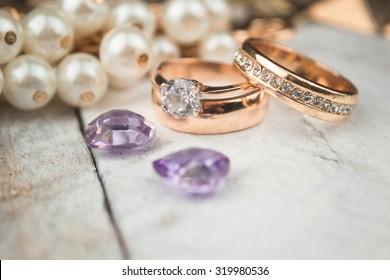 Golden wedding rings on white wood background