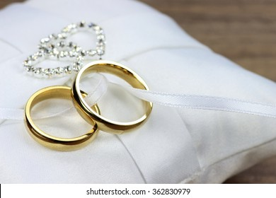 golden wedding rings on white ring bearer pillow
