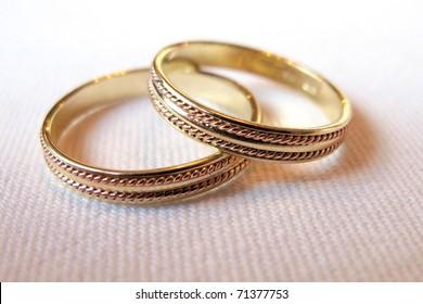 Golden wedding rings on white matter