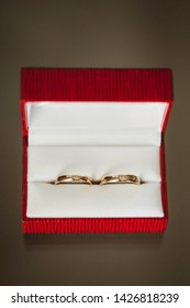 Golden wedding rings in red box on gray fabric background.