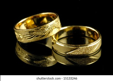 Golden wedding rings with reflection in isolated black background