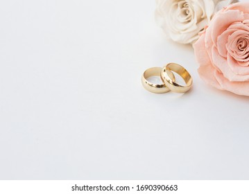 Golden wedding rings and two roses in soft tones on white background