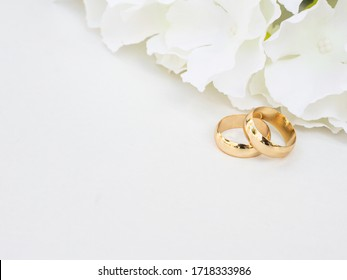 Golden wedding rings and white flowers on white background.
