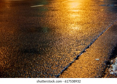 golden wet asphalt at night illuminated by a street lamp as textured background